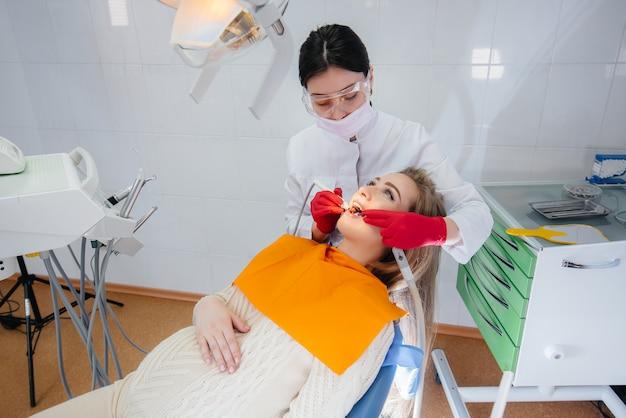 Professionele tandarts behandelt en onderzoekt de mondholte van een zwanger meisje in een moderne tandartspraktijk. tandheelkunde
