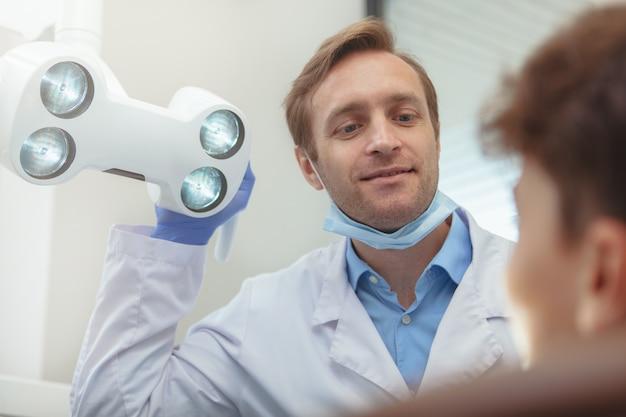 Professionele tandarts die tandlamp aanpassen alvorens tanden van een jonge jongen te onderzoeken