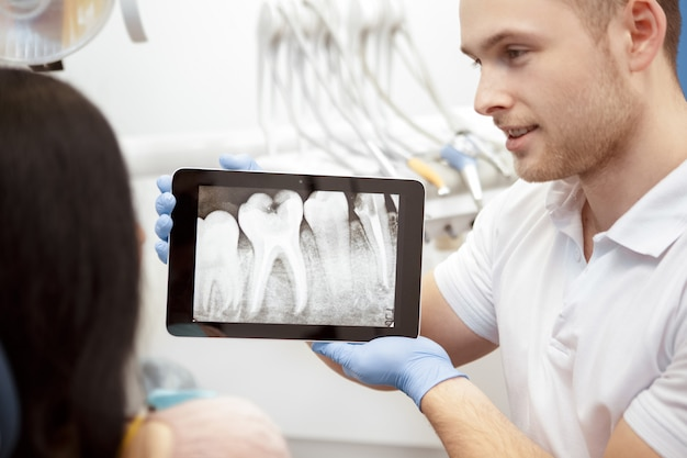Professionele tandarts die zijn cliëntröntgenstralen op een digitale tablet toont
