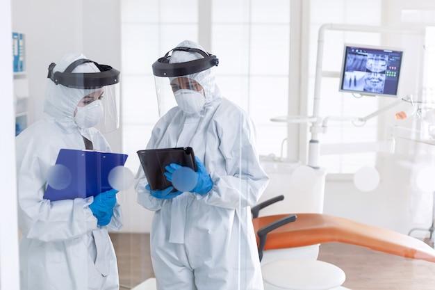 Professionele tandartsen die tablet-pc gebruiken, gekleed in pbm-pak als veiligheidsmaatregel voor covid19. stomatologieteam in tandartspraktijk met beschermend pak tegen besmettelijk coronavirus tijdens wereldwijde pande