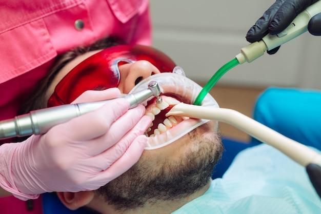 Professionele tandenreiniging, tandarts reinigt de tanden van een mannelijke patiënt.
