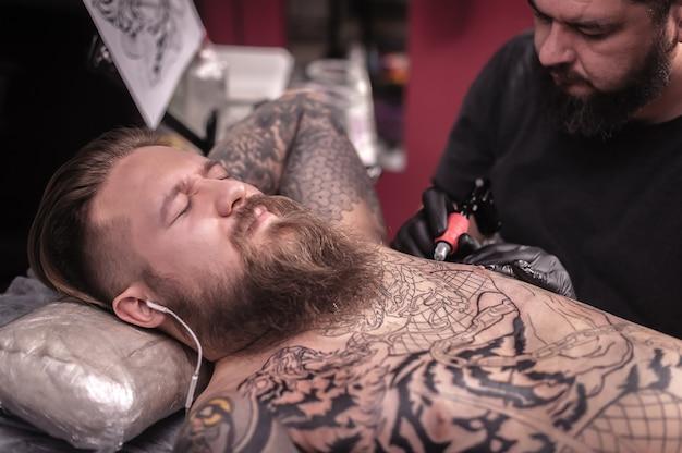 Professionele tatoeëerder demonstreert het proces van het krijgen van een tatoeage