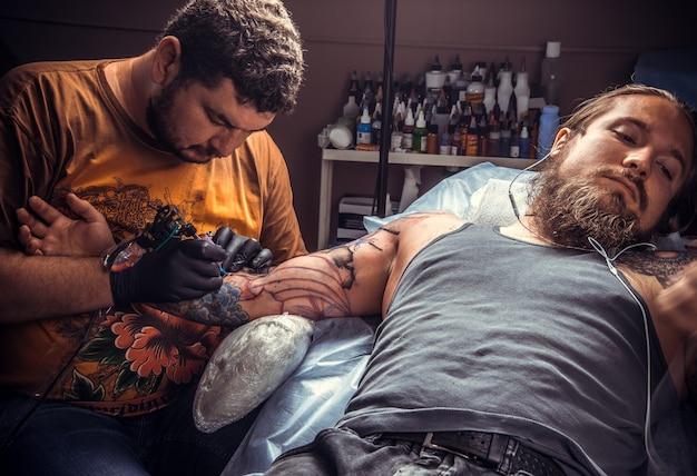 Professionele tatoeëerder doet tatoeage in tattoo salon