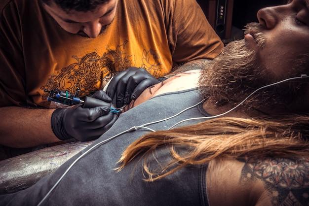 Professionele tatoeëerder doet tatoeage in tattoo studio