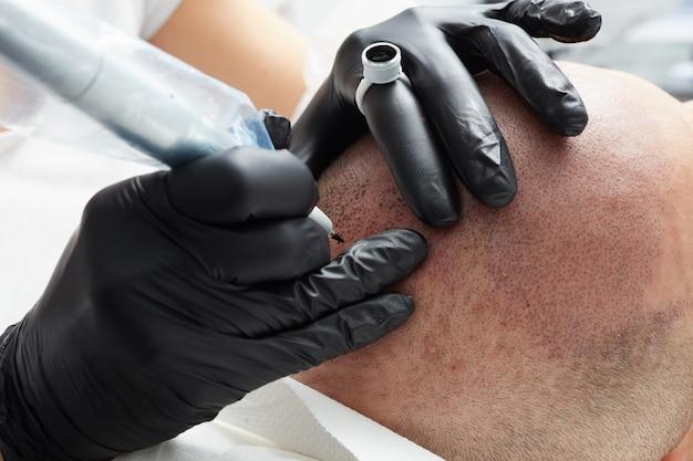 Professionele tatoeëerder maakt permanente make-up tricopigmentatie