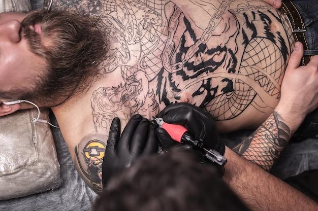 Professionele tatoeëerder maakt tatoeage in een atelierstudio