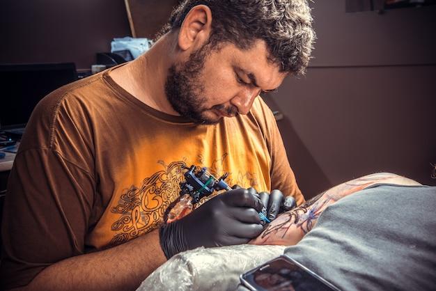 Professionele tatoeëerder maken van een tatoeage in tattoo salon