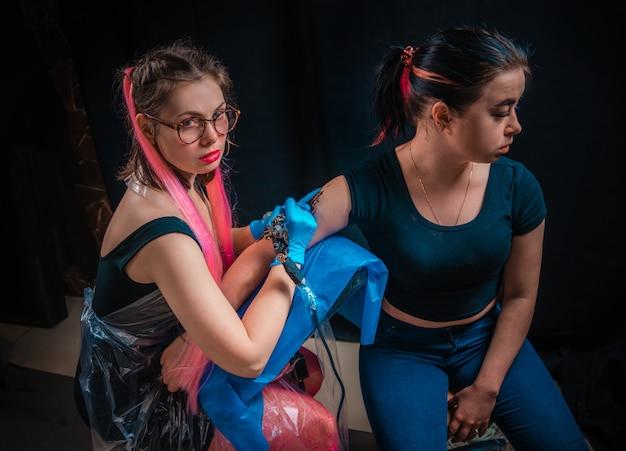 Professionele tatoeëerder toont proces van het maken van een tatoeage