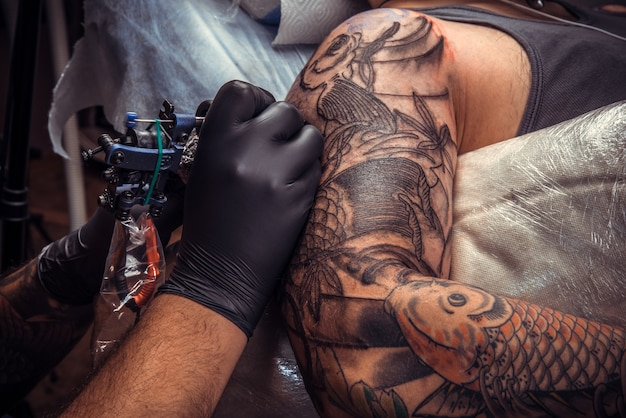 Professionele tatoeëerder werkt in een tattoo-salon