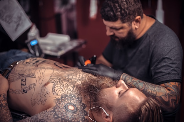 Professionele tattoo-artiest demonstreert het proces om zijn salon te laten tatoeëren