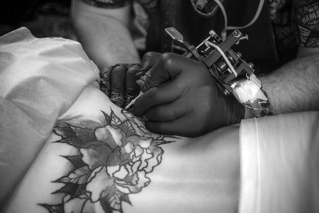 Professionele tattoo-artiest demonstreert het proces van het krijgen van tatoeages in een atelierstudio