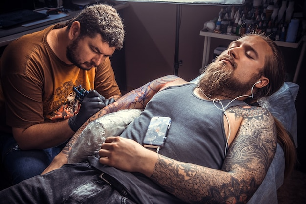 Professionele tattoo-artiest die tatoeëert in een tattoo-salon./tatoeëerder maakt tatoeage in een tattoo-salon.