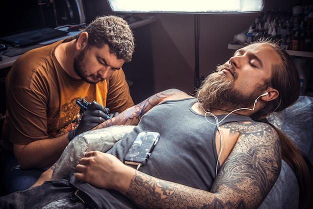 Professionele tattoo-artiest maakt coole tatoeages in tattoo-salon