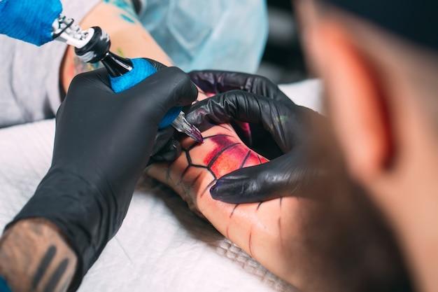 Professionele tattoo-artiest maakt een tatoeage op de hand van een jong meisje.