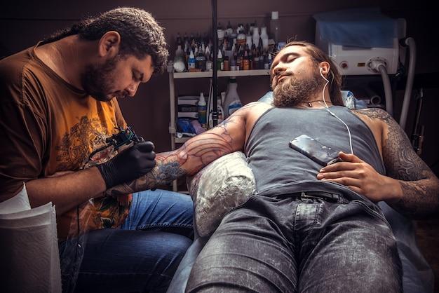 Professionele tattoo-artiest maakt tattoo-foto's in tattoo-salon