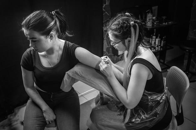 Professionele tattooer concentreerde zich op zijn werk in de salon.