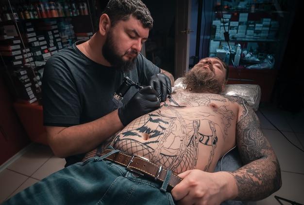 Professionele tattooer tijdens een sessie van de tattoo-artiest in zijn salon.