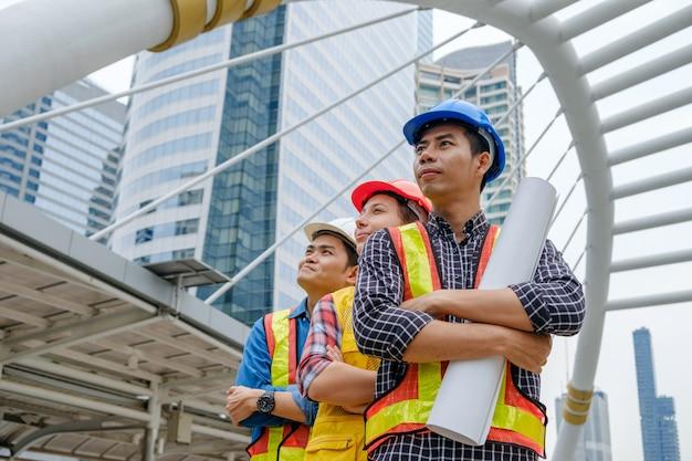 Professionele teamingenieur staande gekruiste armen op wolkenkrabber achtergrond