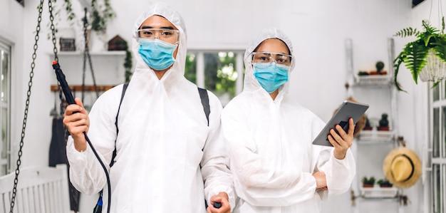 Professionele teams voor desinfectiemedewerker in beschermend masker en wit pak desinfecterend sprayreinigingsvirus voor hulpdienst doden coronavirus bij klant thuis