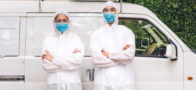 Professionele teams voor ontsmettingsmedewerker in beschermend masker en wit pak desinfecterende sprayreinigingsvirus