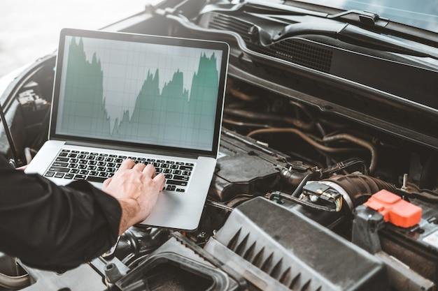 Professionele technicus handen van het controleren van autoreparatiedienst met behulp van laptop op de auto