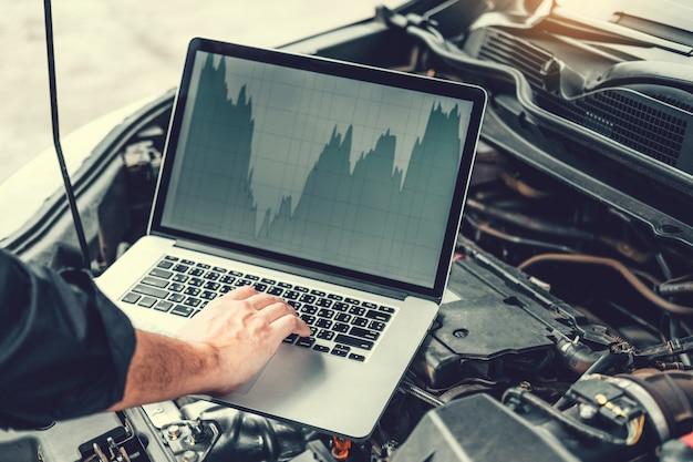 Professionele technicus hands of het controleren van de motor van een autoreparatiedienst die laptop op auto met behulp van