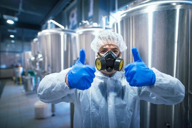 Professionele technoloog expert in beschermend wit uniform met haarnetje, masker en handschoenen die beide duimen omhoog houden