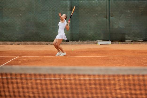 Professionele tennisser tennissen op een tennisbaan van klei op een zonnige dag.