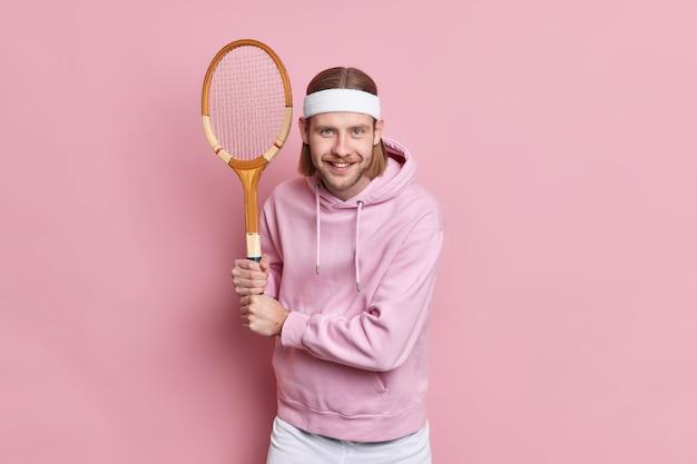 Professionele tennisser vormt in klaar positie vormt op speelveld heeft gelukkige uitdrukking