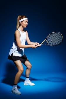 Professionele tennisspeelster met racket klaar om een bal te raken.