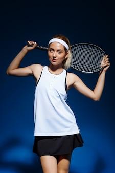 Professionele tennisspeelster met racket op de schouder poseren
