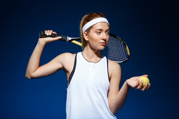 Professionele tennisspeelster met racket op schouder en bal in de hand poseren
