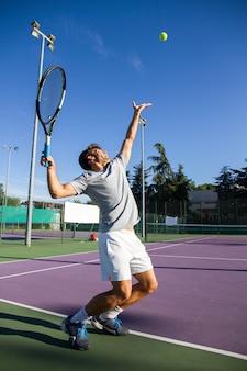 Professionele tennisspeler doet een kicktennis op een tennisbaan op een zonnige zomerdag