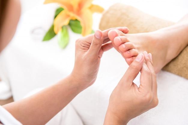 Professionele therapeut die ontspannende reflexology voetmassage geeft aan een vrouw in kuuroord