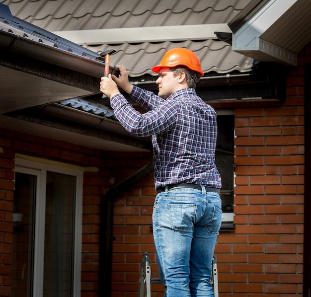 Professionele timmerman die dakplanken hamert met hamer