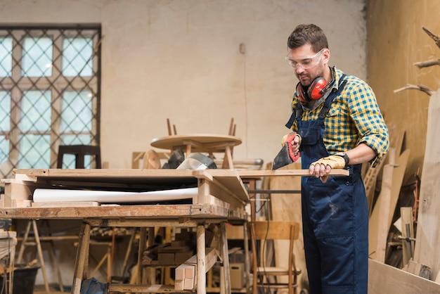 Professionele timmerman die de houten plank met handsaw in de workshop snijdt