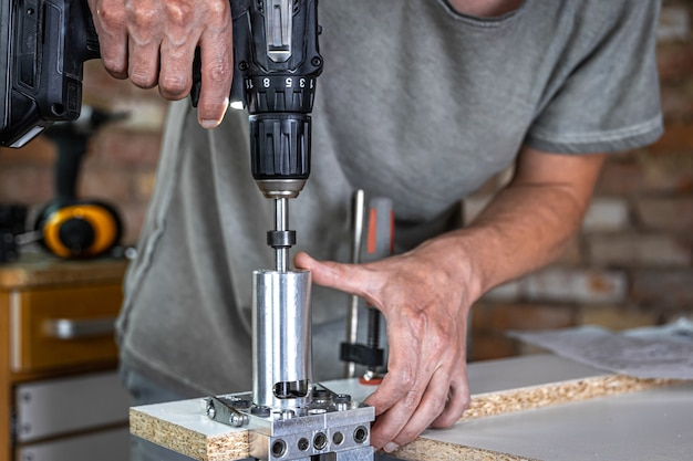 Professionele timmerman die met hout werkt en gereedschappen in huis bouwt.