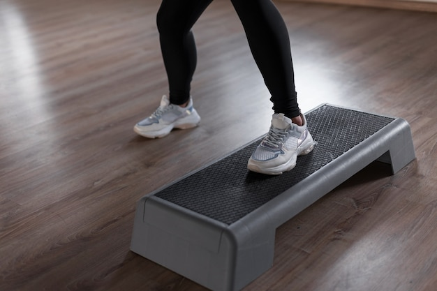 Professionele trainer van de vrouw in stijlvolle sport sneakers in legging die zich bezighouden met fitness op de stap van het platform in de sportschool