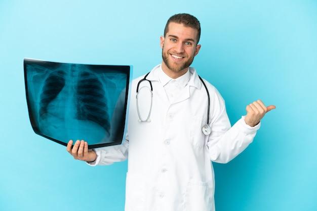 Professionele traumatoloog die op blauwe muur wordt geïsoleerd die naar de kant wijst om een product te presenteren