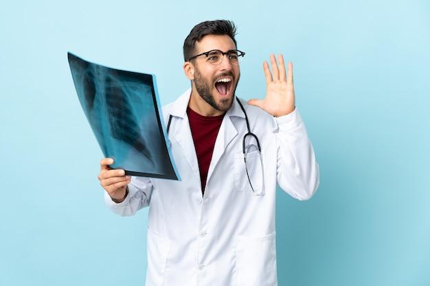 Professionele traumatoloog die radiografie houdt die op blauwe muur wordt geïsoleerd die met wijd open mond schreeuwt