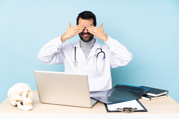 Professionele traumatoloog in werkplek bedekking ogen door handen