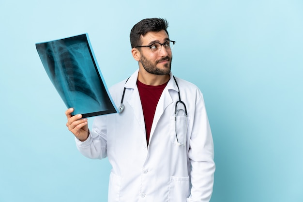Professionele traumatoloog met radiografie geïsoleerd op blauwe muur staan en kijken naar de zijkant