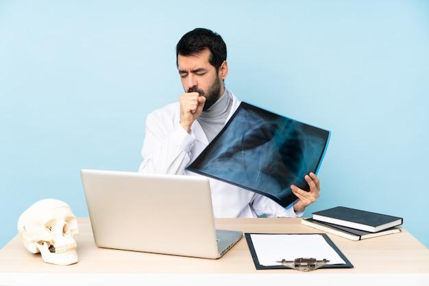 Professionele traumatoloog op de werkplek lijdt aan hoest en voelt zich slecht