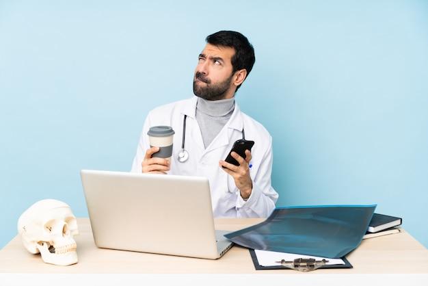 Professionele traumatoloog op de werkplek met koffie om mee te nemen en een mobiel terwijl je iets denkt