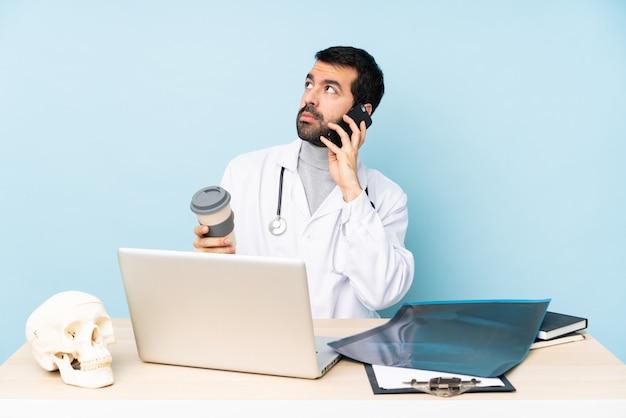 Professionele traumatoloog op de werkplek met koffie om mee te nemen en een mobiel