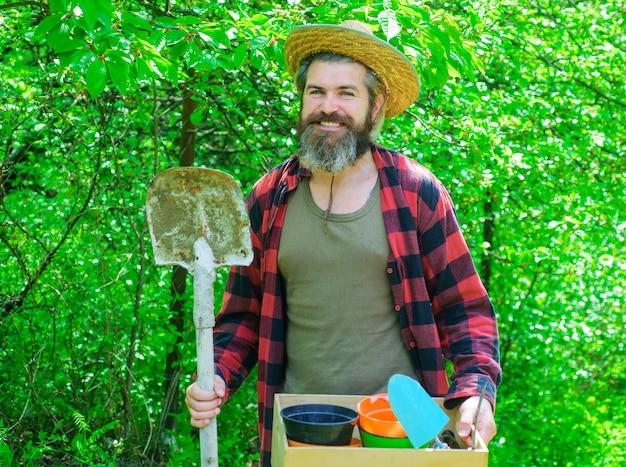 Professionele tuinman. gelukkig bebaarde man in de tuin. eco-boerderij. mannetje met tuingereedschap.