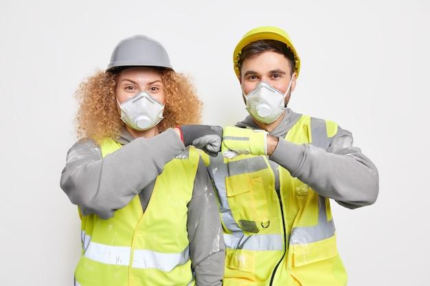 Professionele twee onderhoudsmedewerkers werken in team en maken een vuiststootgebaar