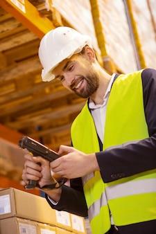 Professionele uitrusting. vrolijke positieve man kijken naar het scanapparaat tijdens het werken met goederen in het magazijn