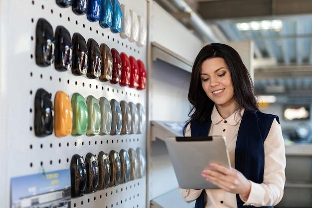 Professionele verkoper helpt om kleur te kiezen voor een auto in dealercentrum
