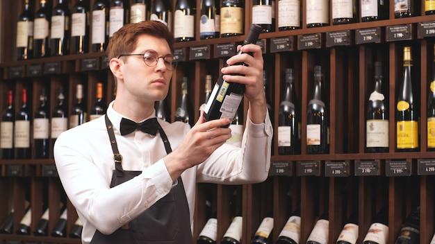 Professionele verkoper selecteert een fles wijn voor u, afhankelijk van het land van herkomst en vintage